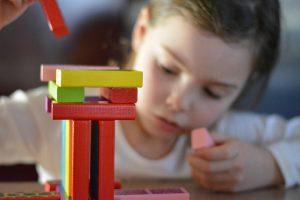 Meisje speelt met houten blokken - Gewoon Opgeruimd