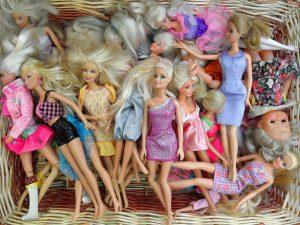 Verschillende Barbies in een mand. Leer kind speelgoed opruimen - Gewoon Opgeruimd
