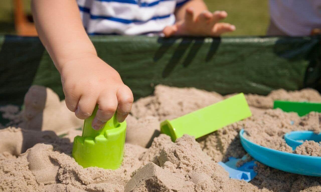 kind speelt in zandbak - tips tuin opruimen met kinderen